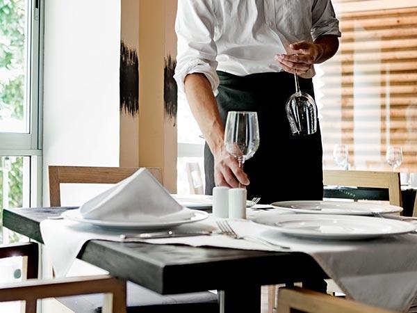 camarero con copa en la mano preparando mesa para clientes