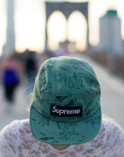 Chica llevando una gorra Supreme en estampado verde turquesa