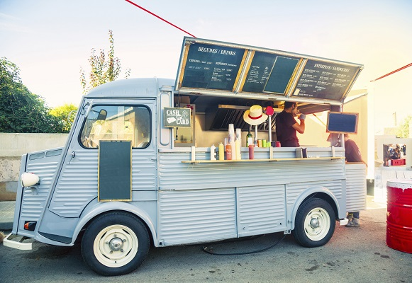 Camioneta de food truck ofreciendo distintos platos de comida de diseño.