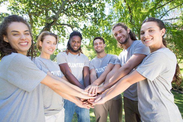 Un grupo de voluntarios juntan sus manos en un parque