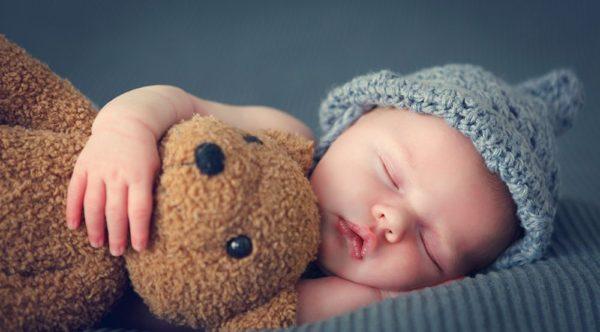 Bebé dormido con oso de peluche