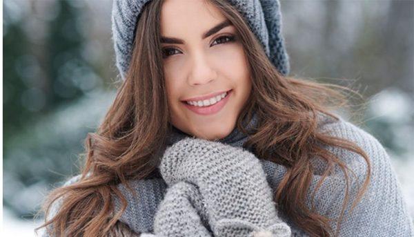 Chica sonriendo con gorro de lana y guantes en color gris