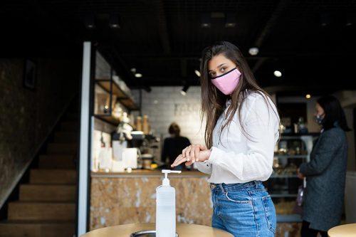mujer con mascarilla se pone gel alcohol en las manos