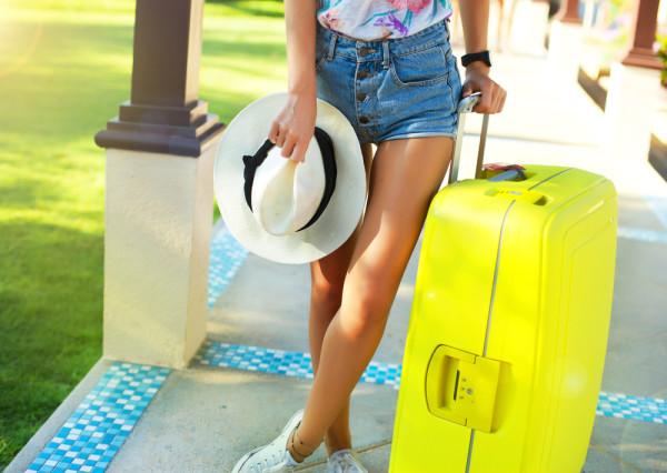 Chica con su maleta trolley amarillo flúor preparada para viajar