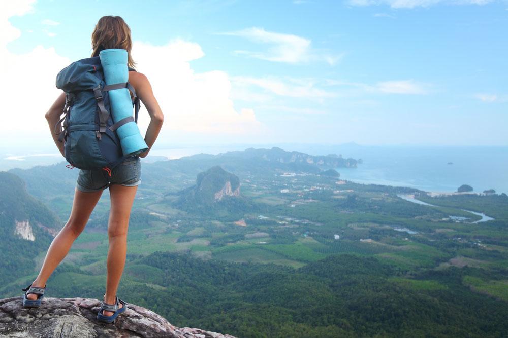 Una joven con una mochila de montaña y una esterilla mira un paisaje desde lo alto de una cima.