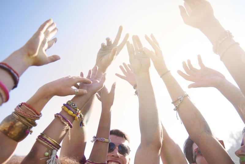 Un grupo de jóvenes en un festival de música de verano elevan sus manos al aire portando distintas pulseras promocionales.