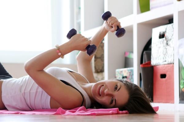 Chica utilizando sus accesorios de fitness en casa