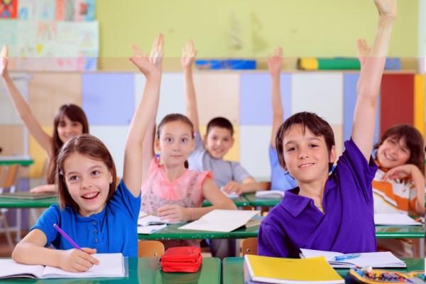 Niños en clase con su material escolar personalizado