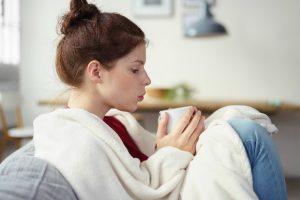 Chica en el sofá con su manta publicitaria blanca tomándose un té