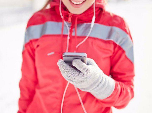 Chica con guantes táctiles utilizando su móvil mientras hace deporte