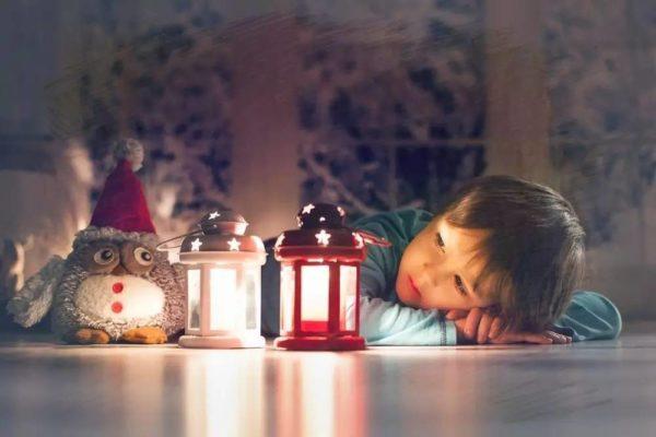Niño con un búho de peluche y dos velas decorativas encendidas de noche