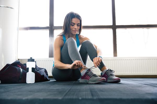 Chica sentada en el suelo atándose las zapatillas con su shaker
