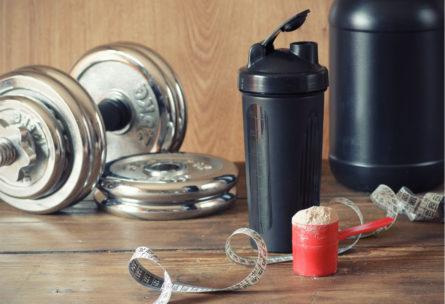 Shaker en color negro junto con pesas y una cinta métrica